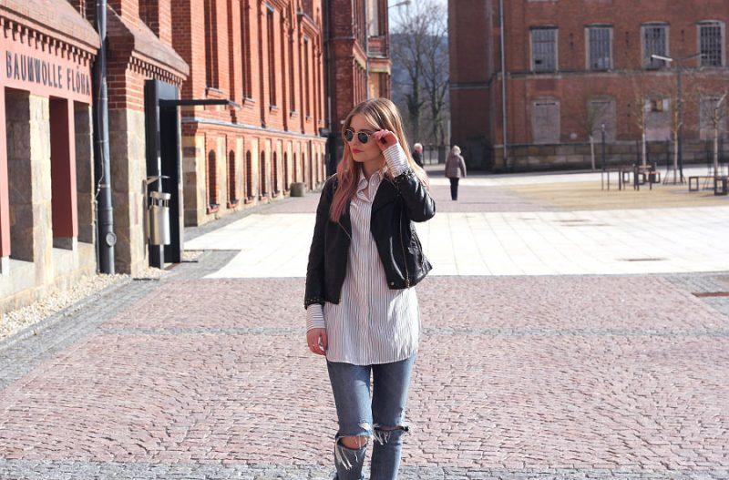 Outfit Frühling mit Lederjacke zerissener Jeans ray ban Sonnenbrille und gestreiftem Hemd
