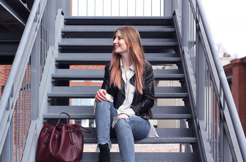Outfit Frühling Lederjacke mit Nieten zerrissene Jeans Boots Hemd mit Streifen Beuteltasche in rot