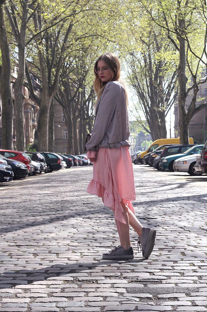 outfit layering im frühling mit rosa volant kleid und bomberjacke, creeper, umhängetasche goldene brille