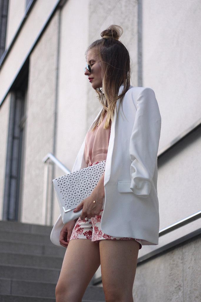 outfit weißer blazer mit blumen shorts und rose bluse mit clutch und half bun