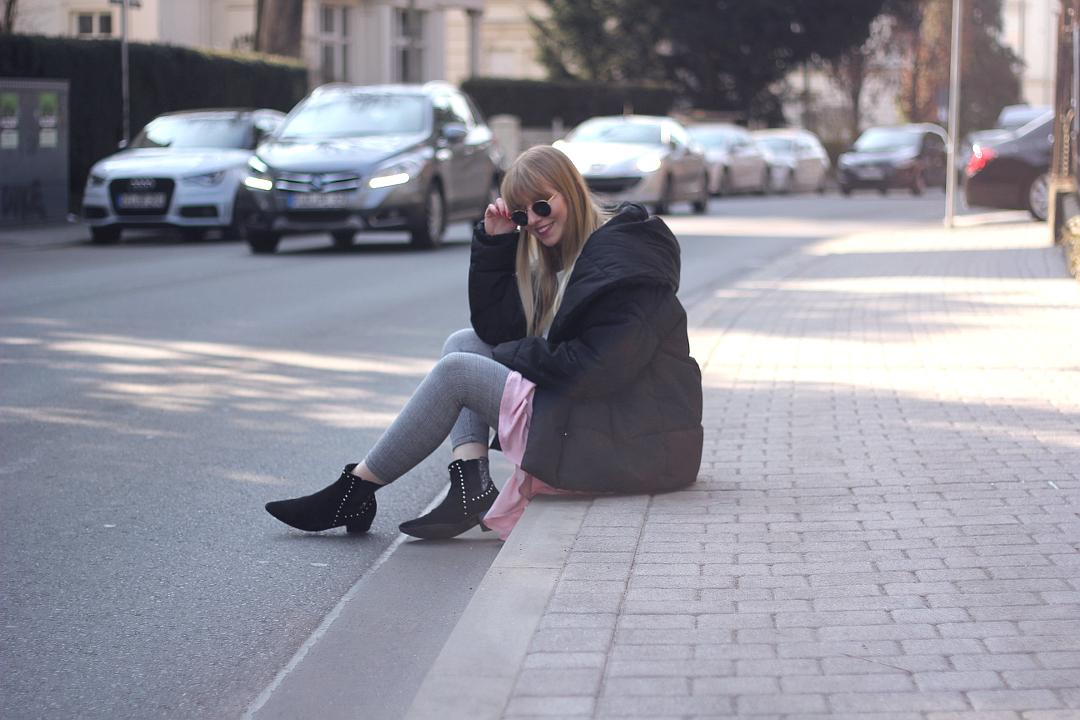 outfit h&m jacke in daunen optik mit stiefeletten karierter leggings und rosa rüschen kleid mit grrauem pulover